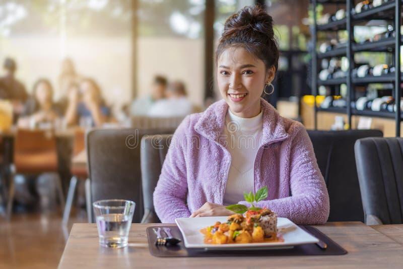 Mujer joven hermosa con la comida en restaurante foto de archivo