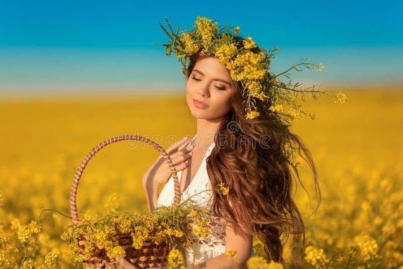 Mujer joven hermosa con la guirnalda en el pelo sano largo sobre fondo amarillo del paisaje del campo de la violación Muchacha mo imagen de archivo