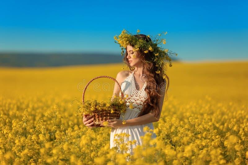 Mujer joven hermosa con la guirnalda en el pelo sano largo sobre fondo amarillo del paisaje del campo de la violación Muchacha mo foto de archivo libre de regalías