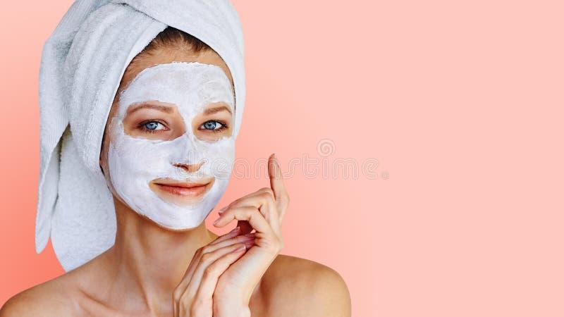 Mujer joven hermosa con la m?scara facial en su cara Cuidado y tratamiento de piel, balneario, belleza natural y concepto de la c fotografía de archivo
