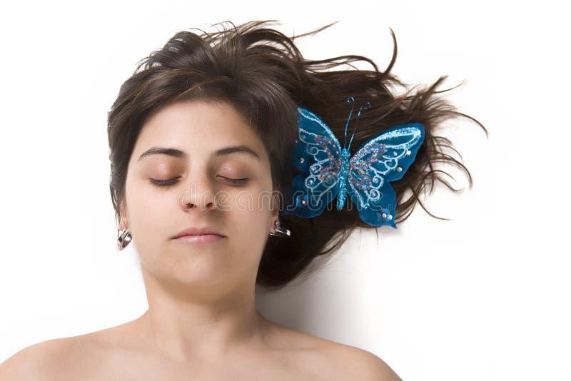 Mujer joven hermosa con la mariposa en el pelo imagen de archivo