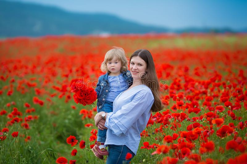 Mujer joven hermosa con la muchacha del niño en campo de la amapola familia feliz que se divierte en naturaleza retrato al aire l imagenes de archivo