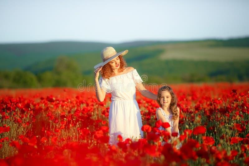 Mujer joven hermosa con la muchacha del ni?o en campo de la amapola familia feliz que se divierte en naturaleza retrato al aire l fotografía de archivo