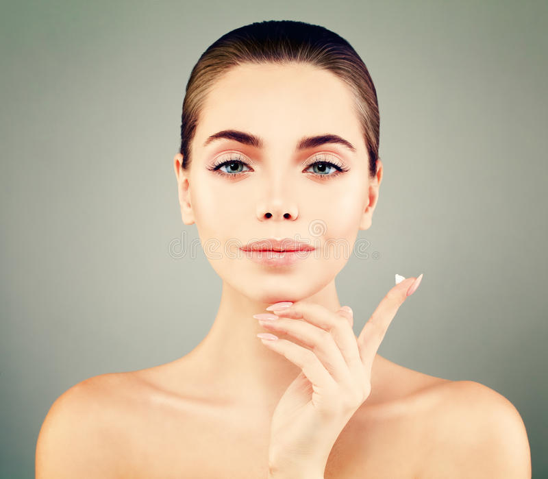 Mujer joven hermosa con la piel fresca limpia que lleva a cabo el descenso poner crema fotografía de archivo libre de regalías