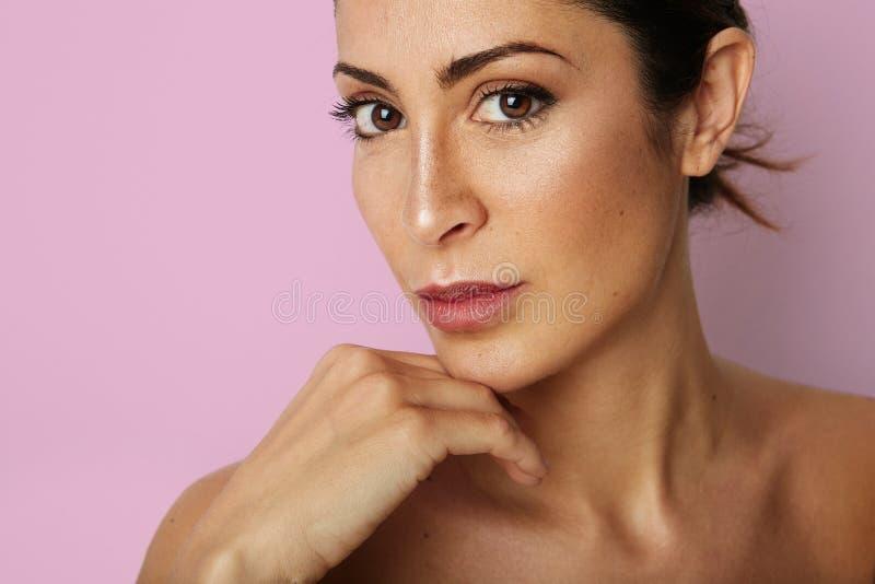 Mujer joven hermosa con la piel limpia, maquillaje natural sobre fondo rosado vacío del color Ciérrese encima del retrato Moda y imagen de archivo