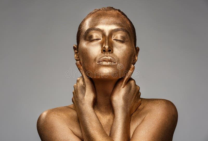 Mujer joven hermosa con la pintura de oro en su cuerpo contra fondo gris imagenes de archivo