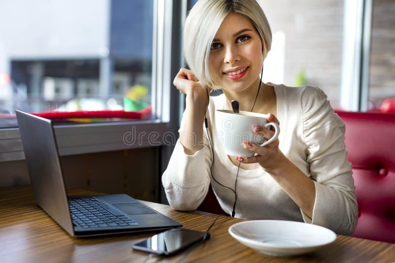 Mujer joven hermosa con la taza de café y el ordenador portátil en café imagenes de archivo