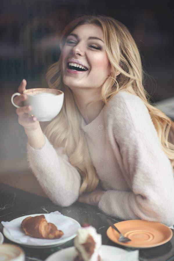 Mujer joven hermosa con la taza de consumición larga rubia del pelo de coff fotografía de archivo