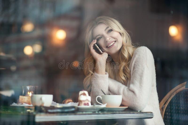 Mujer joven hermosa con la taza de consumición larga rubia del pelo de coff imágenes de archivo libres de regalías