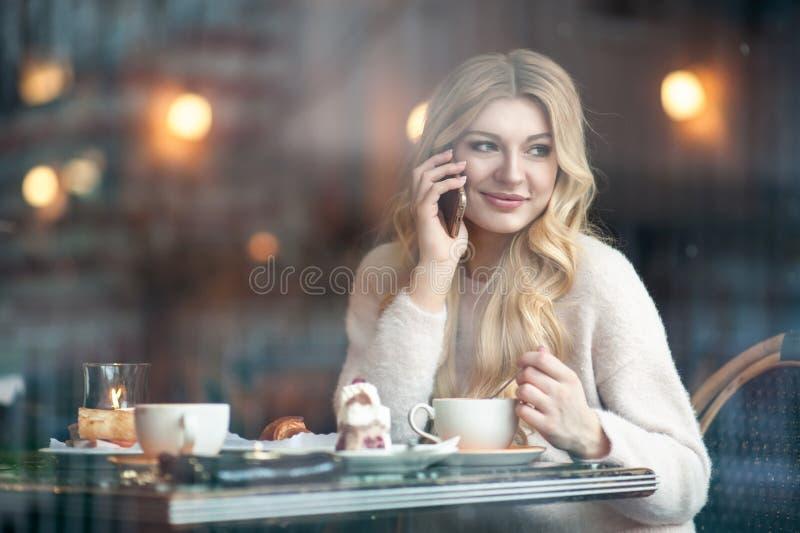 Mujer joven hermosa con la taza de consumición larga rubia del pelo de coff imagen de archivo