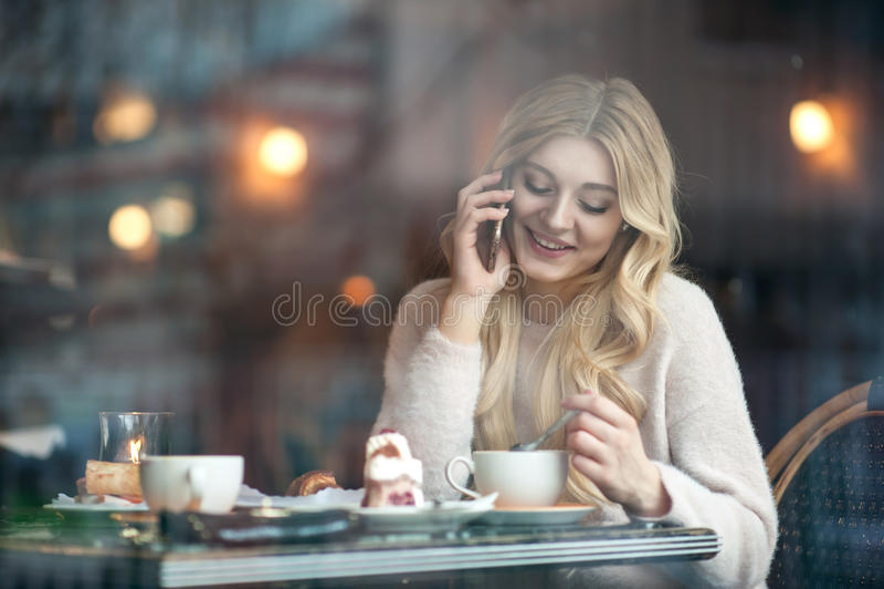 Mujer joven hermosa con la taza de consumición larga rubia del pelo de coff imagen de archivo libre de regalías