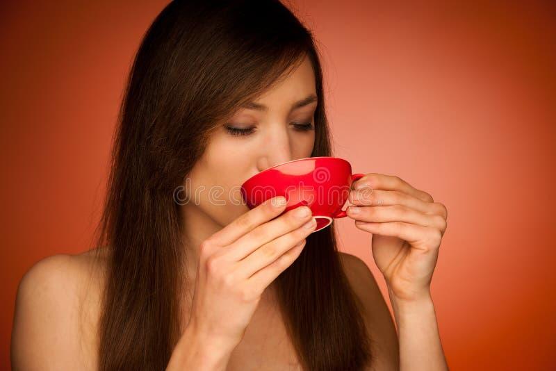 Mujer joven hermosa con la taza de té en sus manos imagenes de archivo