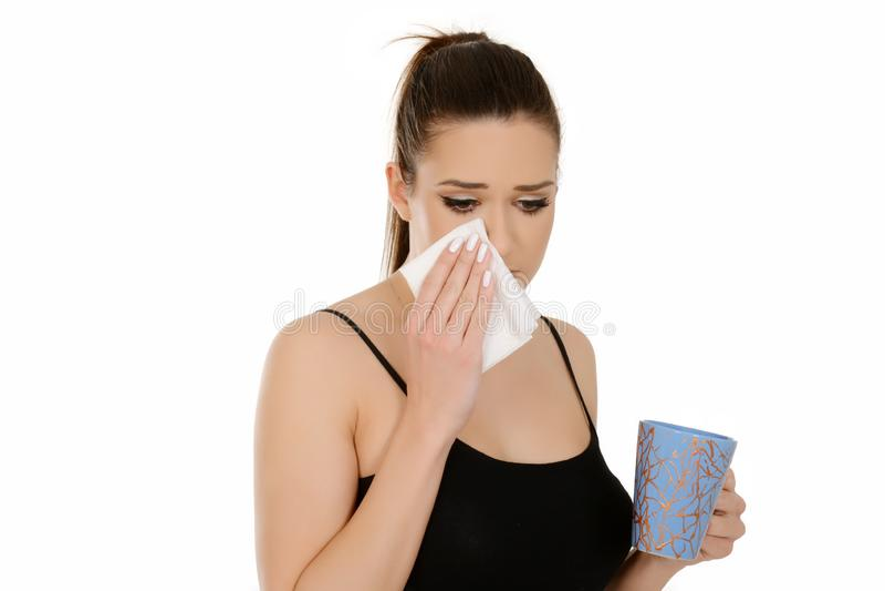 Mujer joven hermosa con la taza y el tejido de la tenencia de la cola de potro, teniendo gripe imagen de archivo