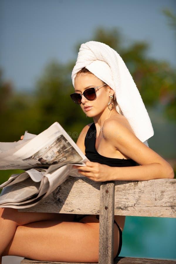 Mujer joven hermosa con la toalla en su periódico n de la lectura del pelo imagenes de archivo