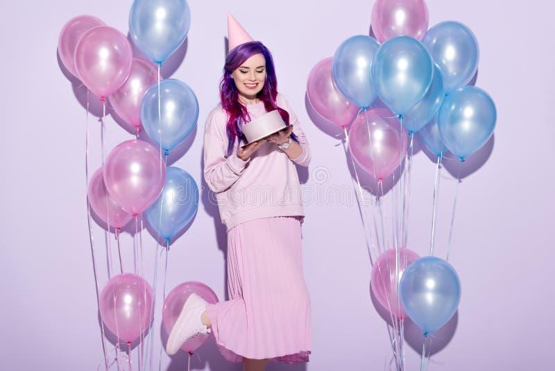 mujer joven hermosa con la torta de cumpleaños y el sombrero del partido fotos de archivo libres de regalías