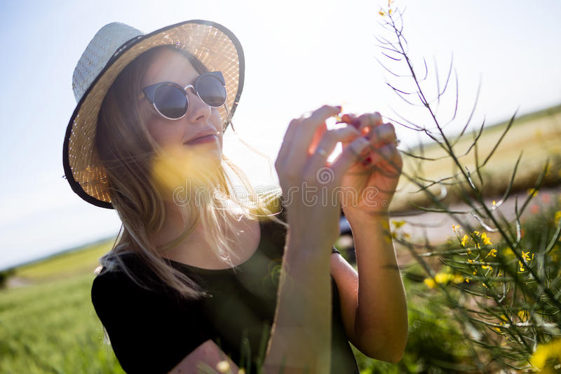 Mujer joven hermosa con las flores que disfruta de verano en un campo fotografía de archivo libre de regalías