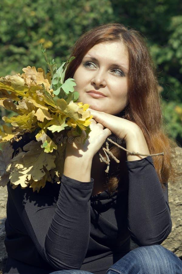 Mujer joven hermosa con las hojas de otoño en parque imágenes de archivo libres de regalías