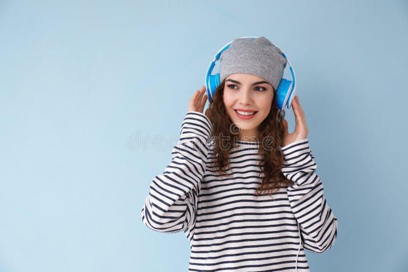 Mujer joven hermosa con los auriculares que escucha la música en fondo del color imagenes de archivo