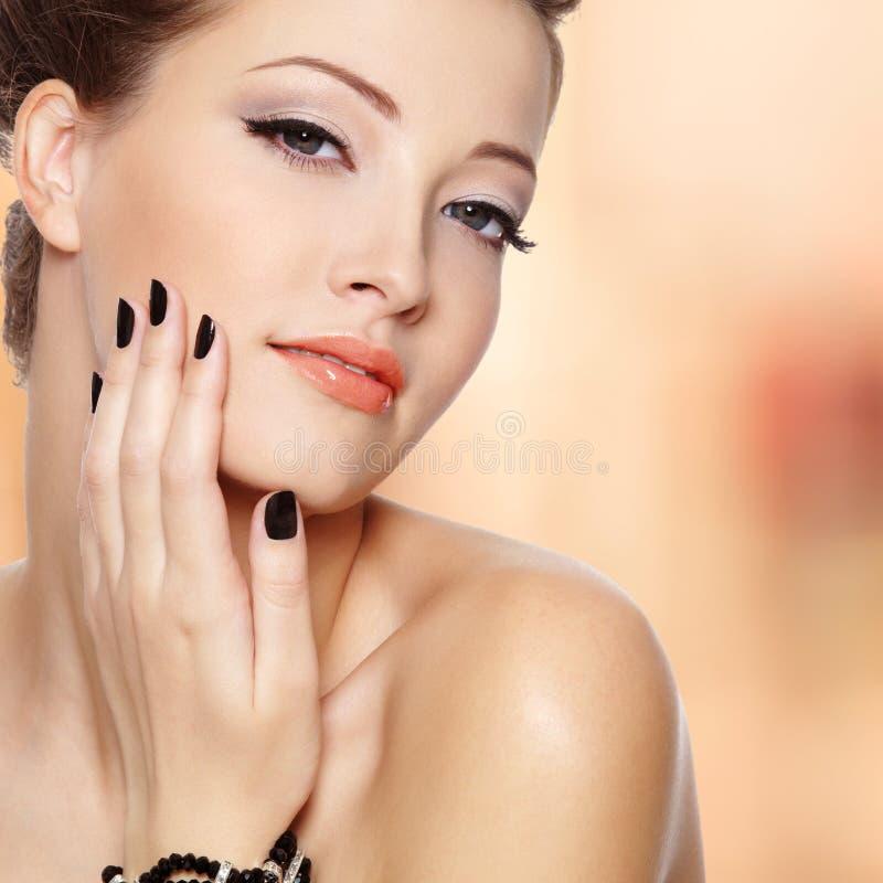 Mujer joven hermosa con los clavos negros fotos de archivo