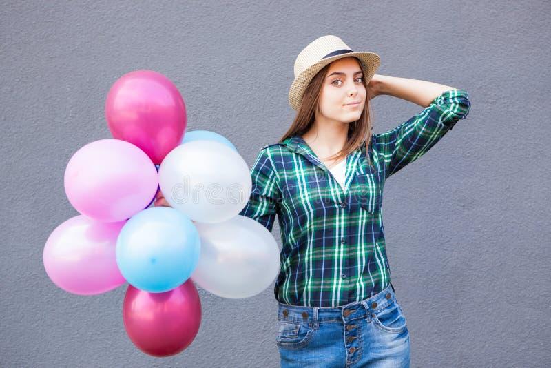 Mujer joven hermosa con los globos cerca de la pared gris fotografía de archivo