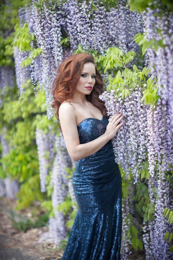Mujer joven hermosa con los labios rojos en el vestido azul sprakling imagenes de archivo