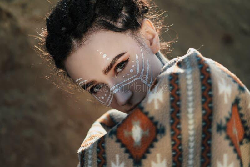 Mujer joven hermosa con los oídos del duende, dreadlocks y un poncho étnico, con la cara pintada Presentación contra una carrera  fotos de archivo libres de regalías