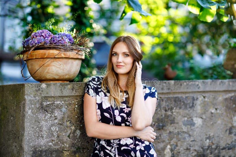 Mujer joven hermosa con los pelos largos en el vestido del verano que va para un paseo en ciudad alemana Muchacha feliz que disfr imagen de archivo libre de regalías