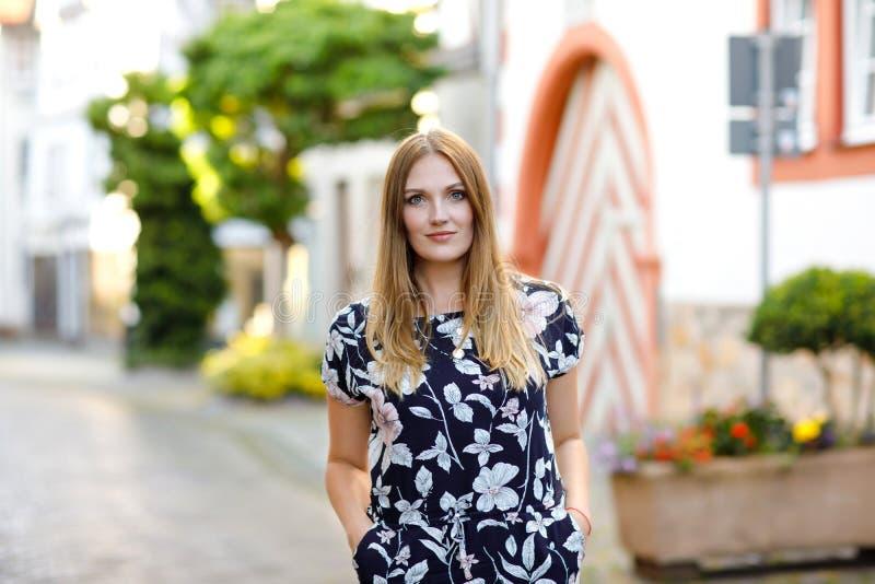 Mujer joven hermosa con los pelos largos en el vestido del verano que va para un paseo en ciudad alemana Muchacha feliz que disfr fotos de archivo