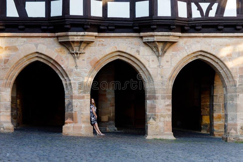 Mujer joven hermosa con los pelos largos en el vestido del verano que va para un paseo en ciudad alemana Muchacha feliz que disfr imágenes de archivo libres de regalías