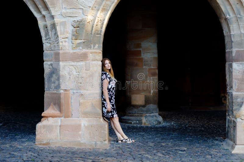 Mujer joven hermosa con los pelos largos en el vestido del verano que va para un paseo en ciudad alemana Muchacha feliz que disfr imagenes de archivo