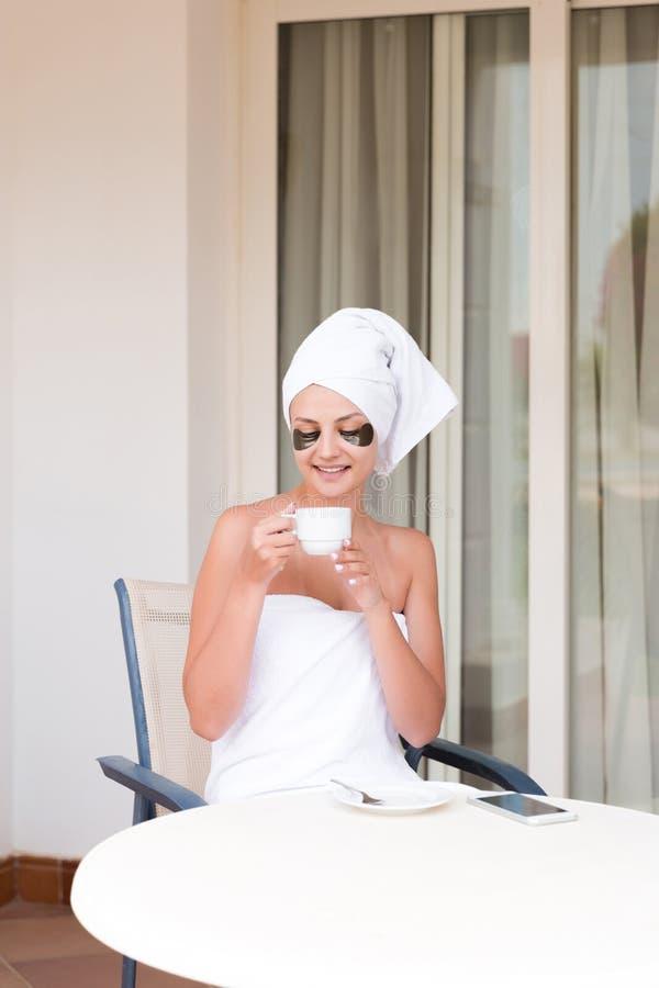 Mujer joven hermosa con los remiendos inferiores del ojo en la taza de la tenencia de la albornoz de consumici?n del caf? y de la imagen de archivo