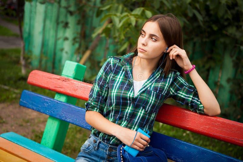 Mujer joven hermosa con música que escucha del pelo largo con los auriculares azules al aire libre fotografía de archivo
