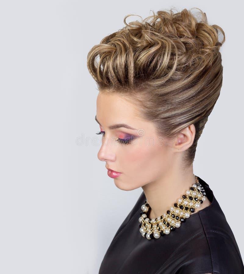Mujer joven hermosa con maquillaje de la tarde y el peinado del salón Ojos ahumados Peinado complicado para el partido foto de archivo libre de regalías