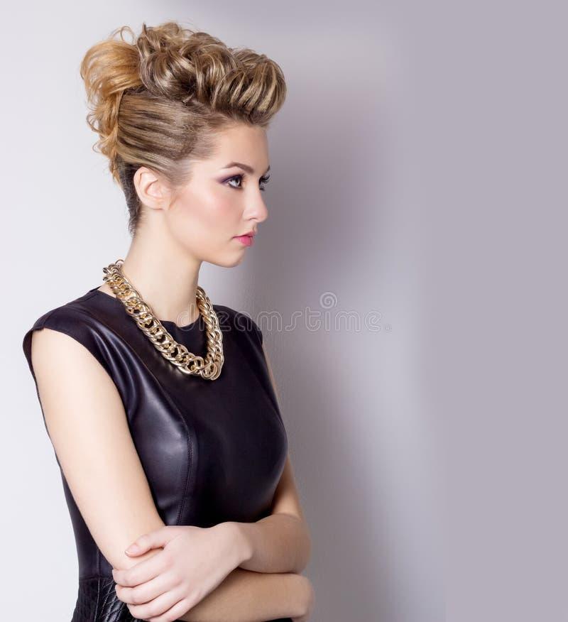 Mujer joven hermosa con maquillaje de la tarde y el peinado del salón Ojos ahumados Peinado complicado para el partido imagenes de archivo
