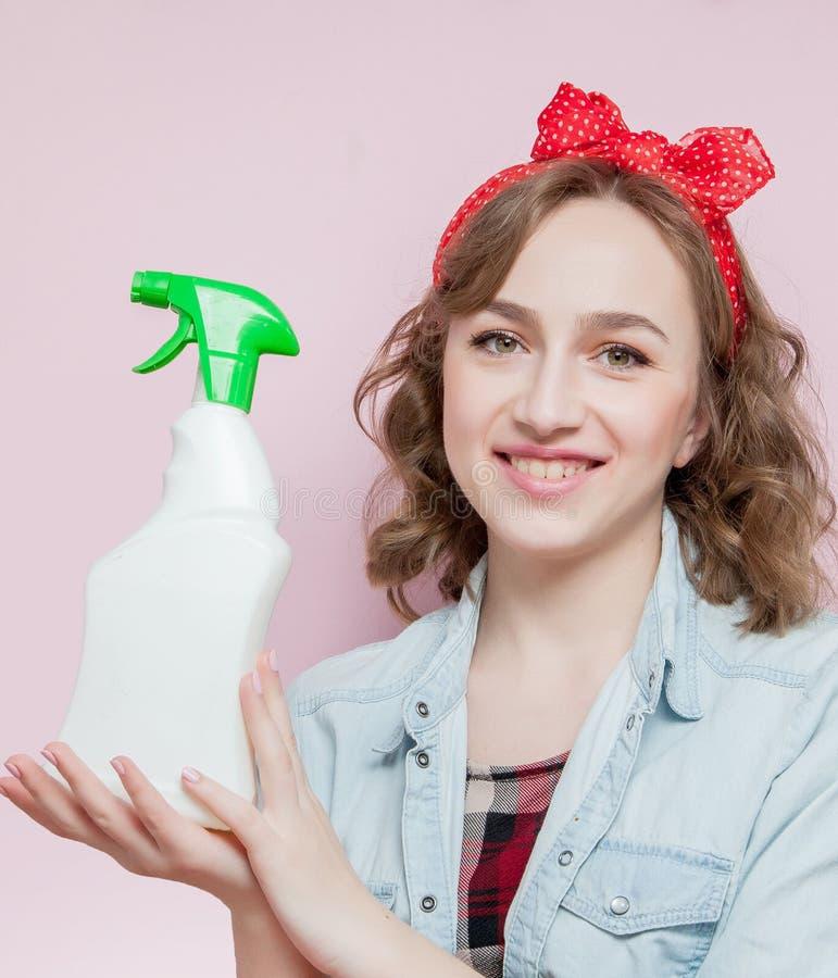 Mujer joven hermosa con maquillaje del perno-para arriba y peinado con las herramientas de limpieza en fondo rosado imagenes de archivo