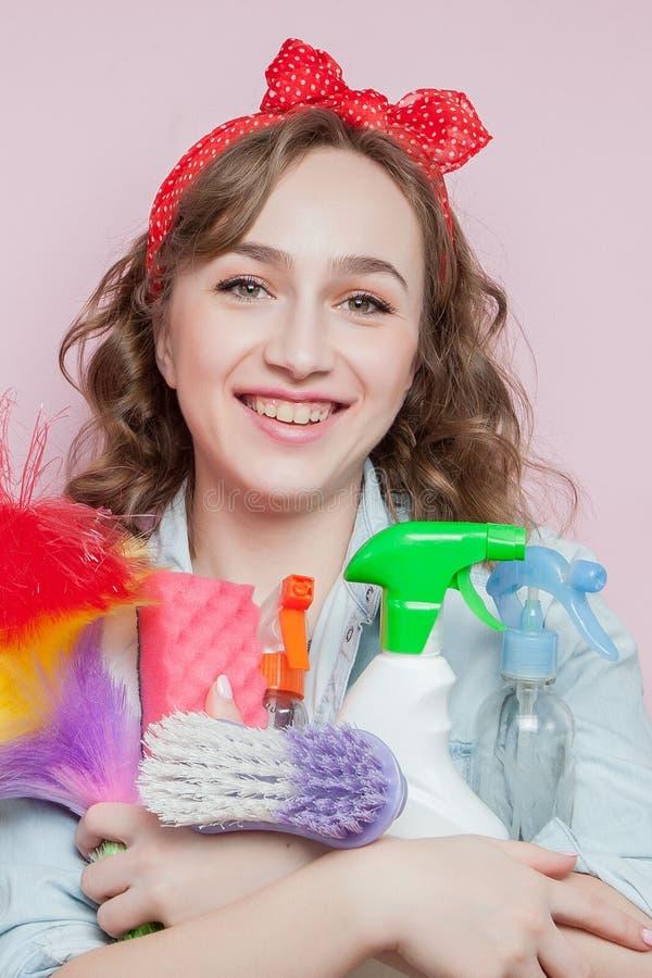 Mujer joven hermosa con maquillaje del perno-para arriba y peinado con las herramientas de limpieza en fondo rosado fotos de archivo libres de regalías