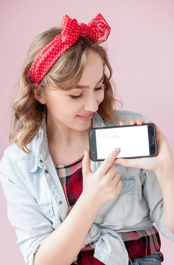 Mujer joven hermosa con maquillaje del perno-para arriba y peinado sobre fondo rosado con el tel?fono m?vil con el espacio de la  foto de archivo libre de regalías