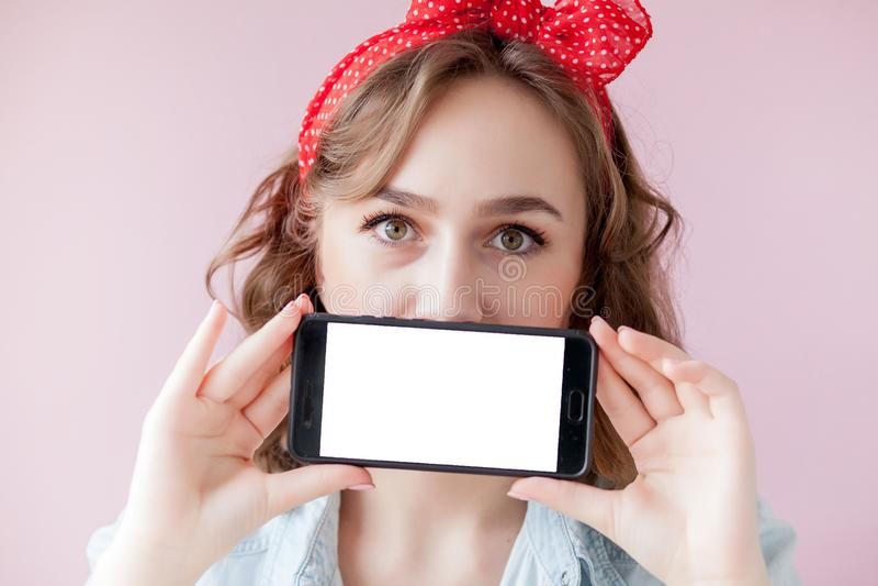 Mujer joven hermosa con maquillaje del perno-para arriba y peinado sobre fondo rosado con el tel?fono m?vil con el espacio de la  foto de archivo