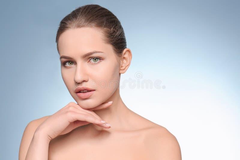 Mujer joven hermosa con maquillaje natural en fondo del color imagenes de archivo