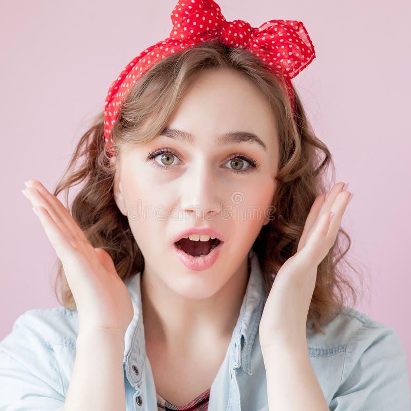 Mujer joven hermosa con maquillaje y el peinado del perno-para arriba Estudio tirado en fondo rosado imágenes de archivo libres de regalías