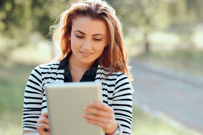 Mujer joven hermosa con Tablet PC que mira el vídeo al aire libre fotos de archivo