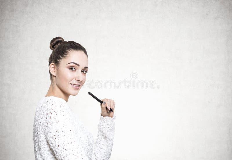 Mujer joven hermosa con un marcador, concreto fotos de archivo libres de regalías