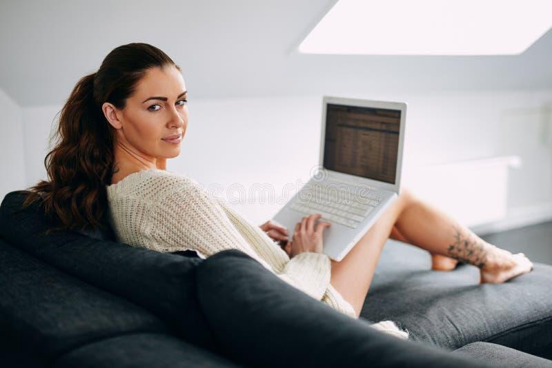 Mujer joven hermosa con un ordenador portátil en el sofá fotografía de archivo libre de regalías