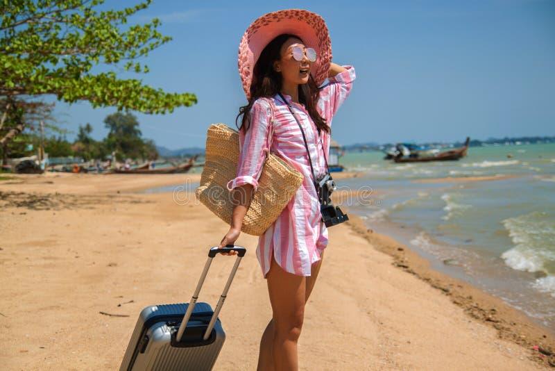 Mujer joven hermosa con un sombrero que se coloca con la maleta en el fondo maravilloso del mar, concepto de hora de viajar foto de archivo