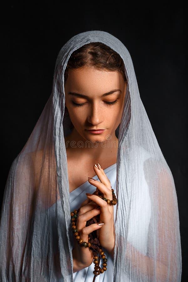 Mujer joven hermosa con una bufanda en su cabeza, y un rosario en sus manos, mirada humilde, mujer de creencia foto de archivo