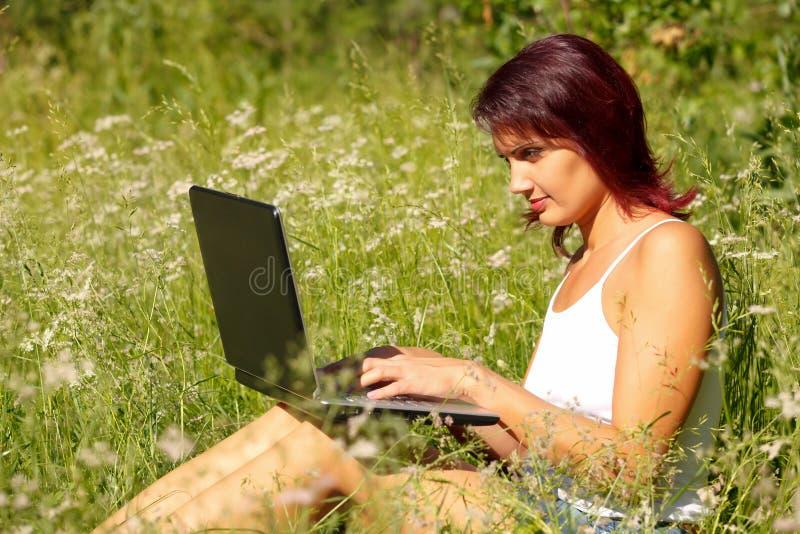 Mujer joven hermosa con una computadora portátil imagenes de archivo