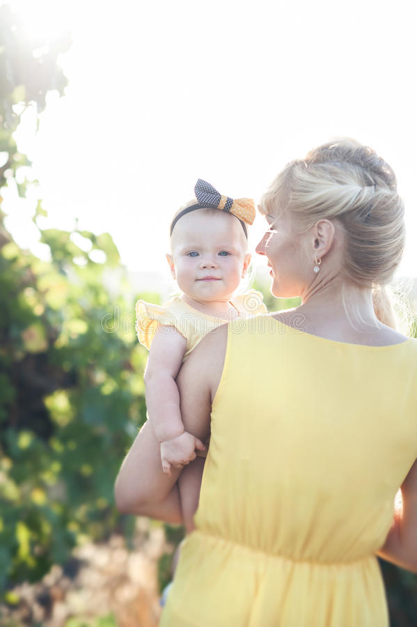 Mujer joven hermosa con una muchacha del niño en el campo de uvas fotografía de archivo libre de regalías