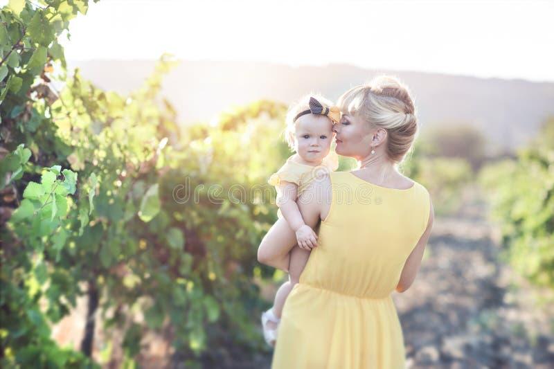 Mujer joven hermosa con una muchacha del niño en el campo de uvas imagen de archivo