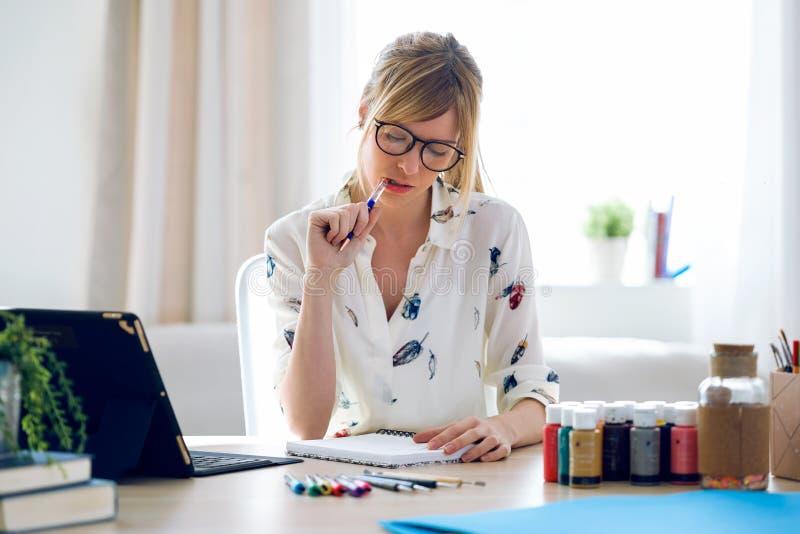 Mujer joven hermosa concentrada del diseñador que piensa en trabajo en la oficina imagen de archivo libre de regalías
