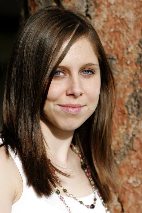 Mujer joven hermosa contra un árbol foto de archivo